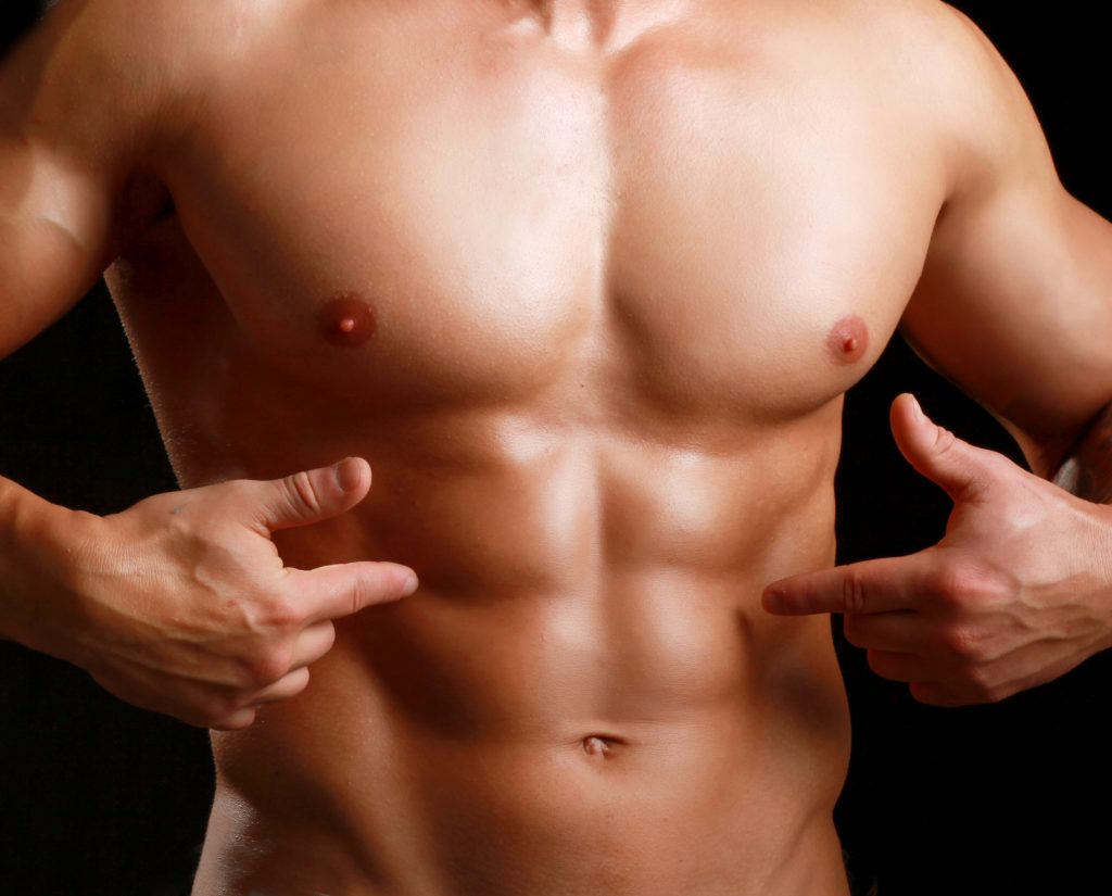 man pointing at his abs