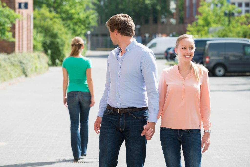 Man with girlfriend looking at another woman