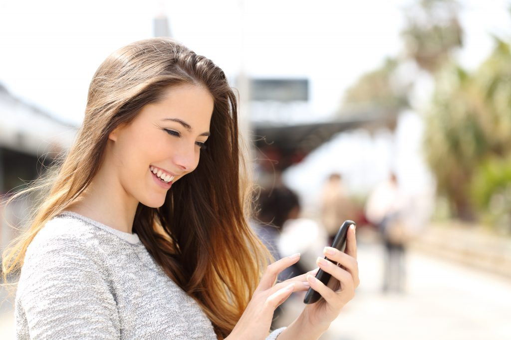 woman smiling at phone