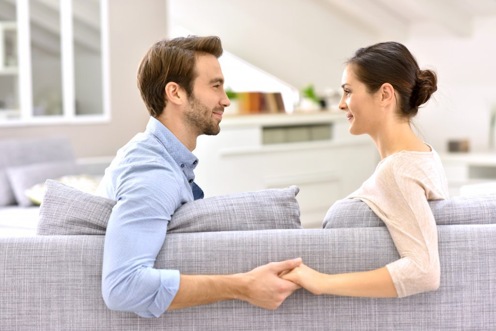 couple holding hands on sofa