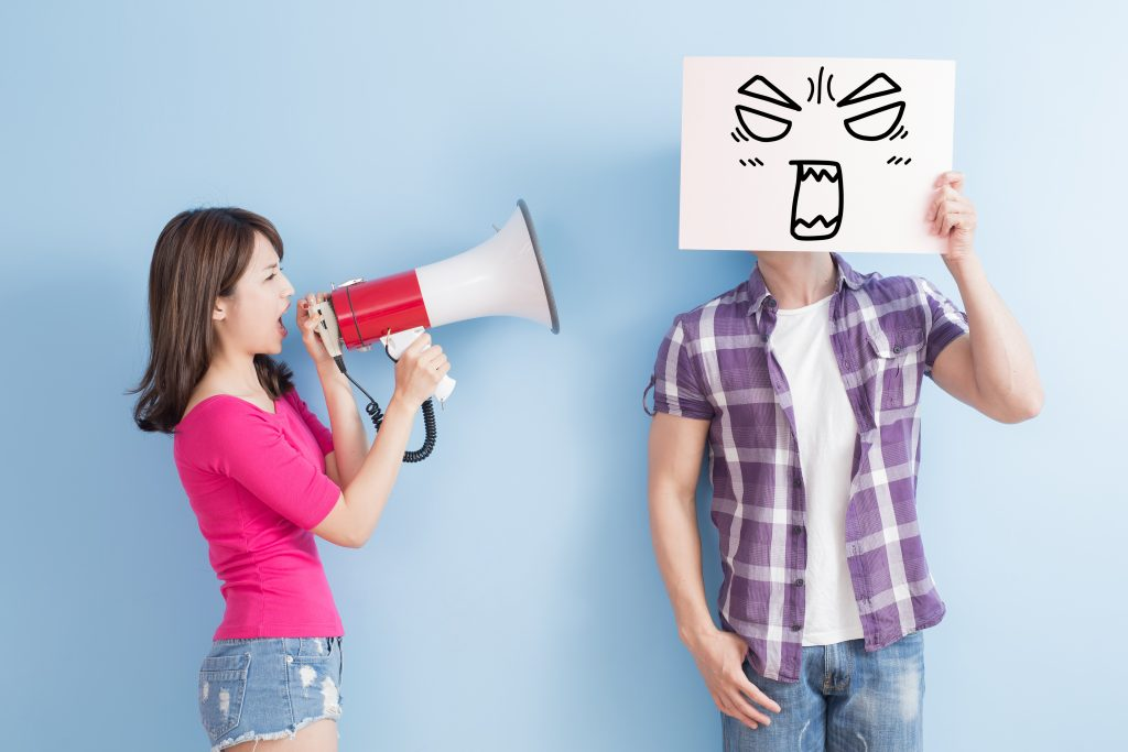 woman shouting at man through megaphone