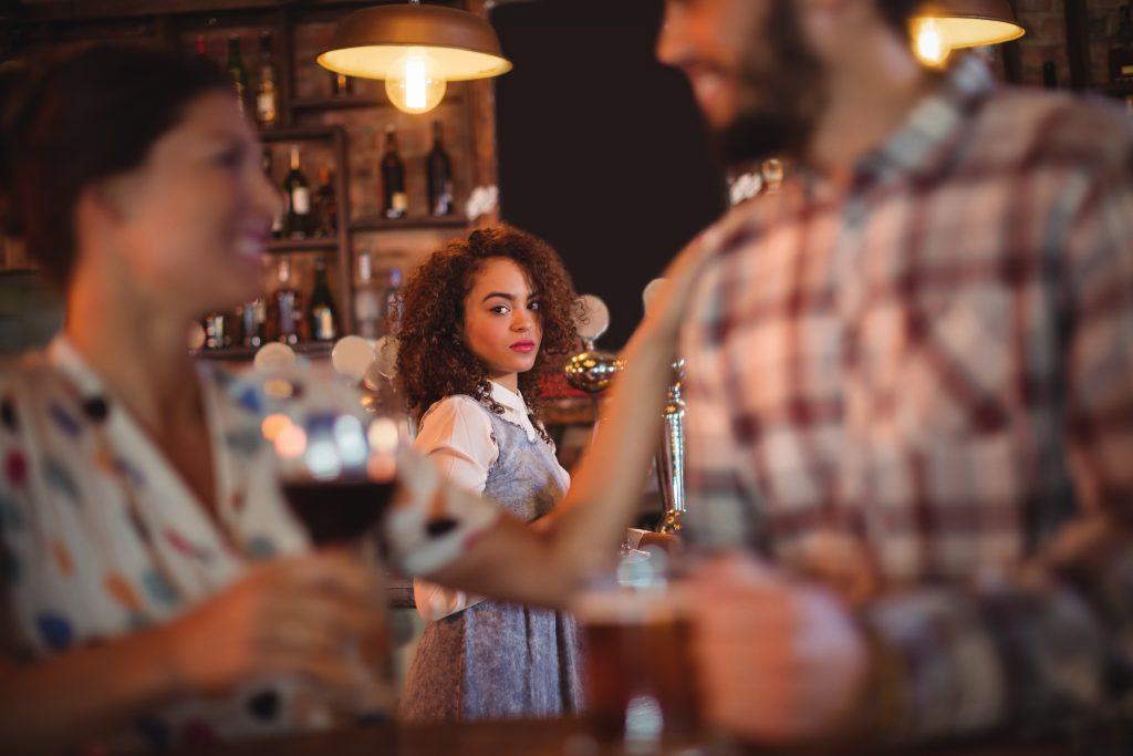 jealous woman at a bar watching couple talk