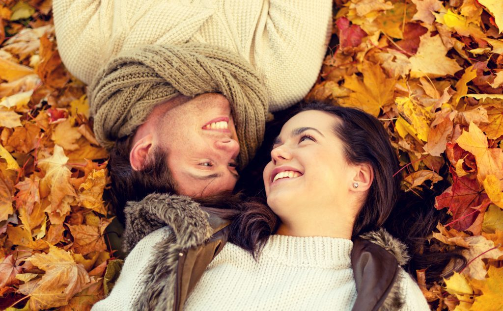 couple laying on leaves