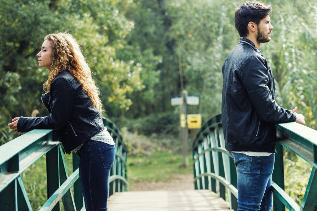 couple standing on bridge looking away from each other