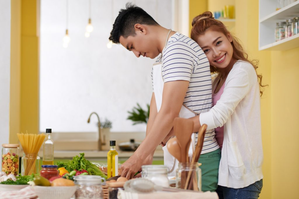 woman hugging man as he cooks
