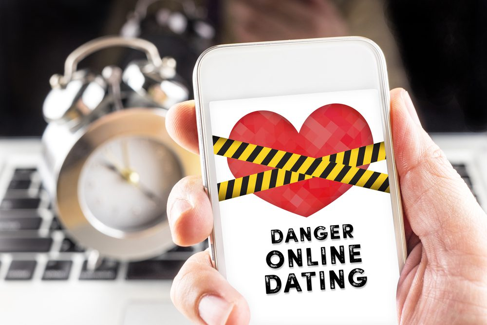 phone screen with warning about online dating