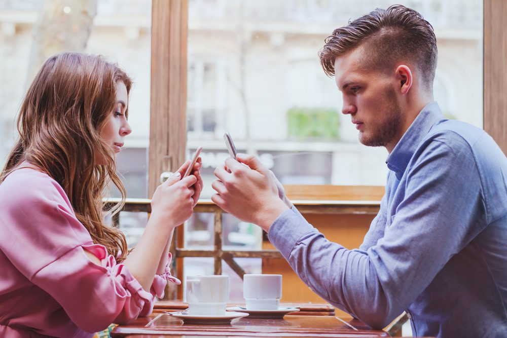man and woman texting at the table