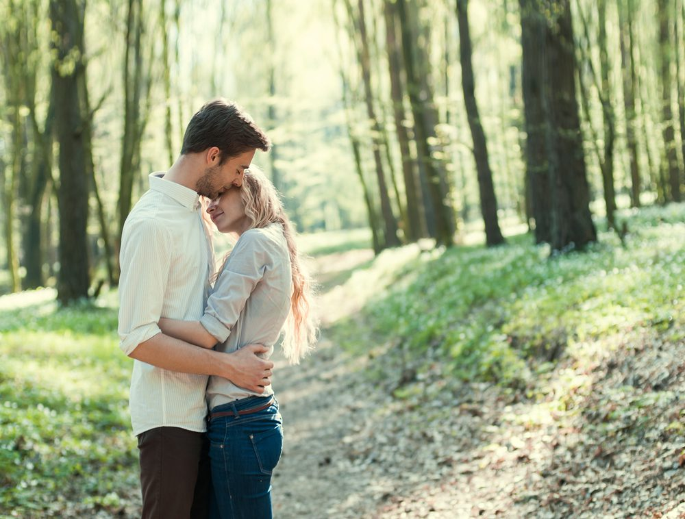 man hugging woman in forest