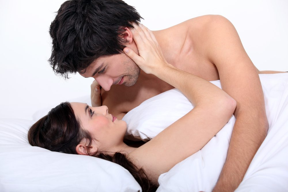 man and woman in bed looking in each other's eyes